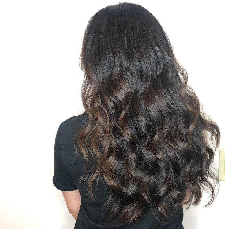 Hair extensions on dark hair done at Fortelli Salon & Spa