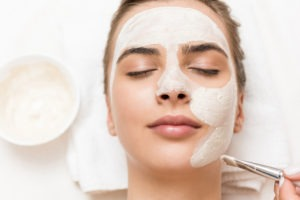 woman relaxing and receiving facial mask and spa therapy