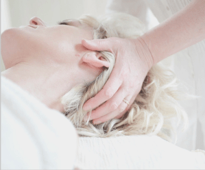 Blond haired woman lying down and receiving a wellness head and neck massage from a professional