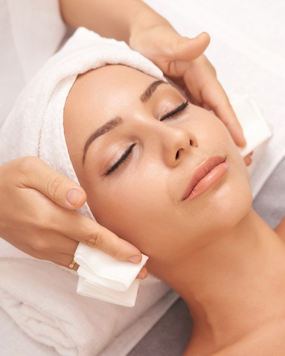Beautiful young woman with flawless skin enjoying professional facial with Microneedling in beauty salon