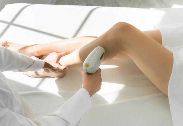 technician applying a laser gun hair removal treatment to a woman lying down with her leg folded